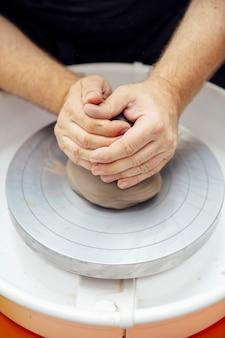 Découvre à un artiste fait la poterie d'argile sur une roue de rotation