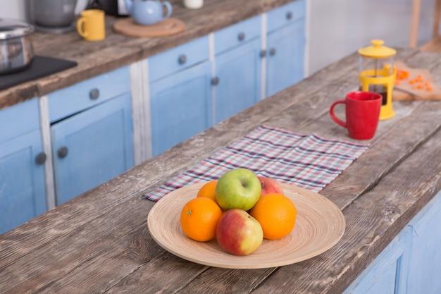 Découvre sur la table en bois à la cuisine avec des fruits et théière à ce sujet.