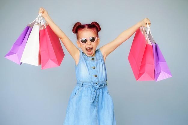 Découvrez les réductions. bonne petite fille sourit avec des sacs en papier.
