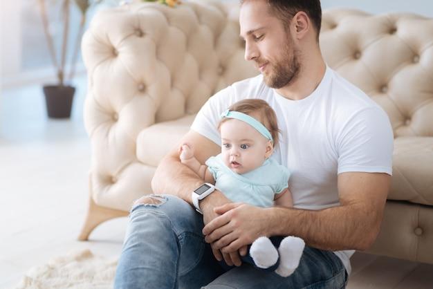 Découvrir un nouveau jour. curieuse petite fille concentrée assise avec son père à la maison et regardant ailleurs tout en exprimant son intérêt