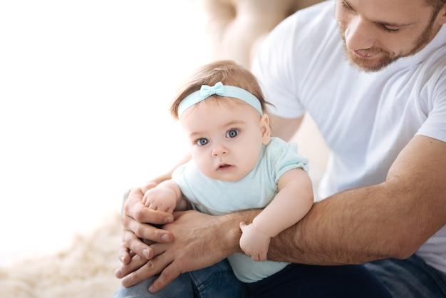 Découvrir de nouvelles choses. curieux petite fille douce couchée dans les mains du jeune père et regardant ailleurs tout en exprimant son intérêt