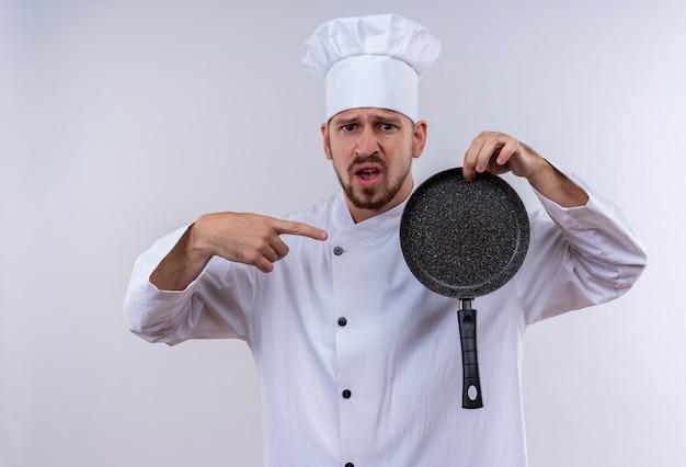 Déçu chef masculin professionnel cuisinier en uniforme blanc et cook hat tenant une casserole pointant avec le doigt sur elle debout sur fond blanc