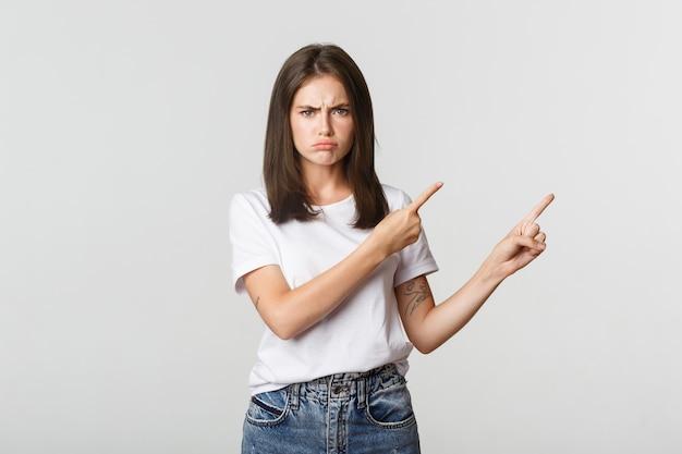 Déçu fille bouder pointant du doigt le coin supérieur droit, fronçant les sourcils et se plaignant.