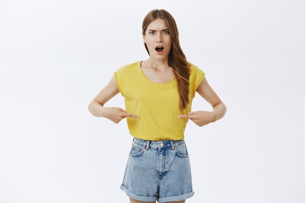 Déçu fille se plaindre pointant sur son ventre, avoir du poids supplémentaire