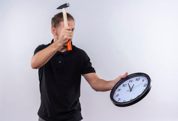 Déçu jeune bel homme en polo noir tenant horloge murale et balançant un marteau va briser l'horloge debout sur fond blanc