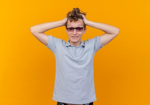 Déçu jeune homme à lunettes noires portant un polo gris touchant sa tête étant confus sur orange