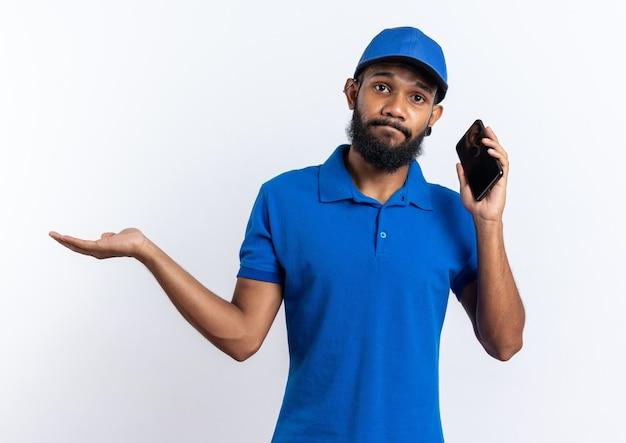 Déçu jeune livreur afro-américain parlant au téléphone et gardant sa main ouverte isolée sur fond blanc avec espace de copie