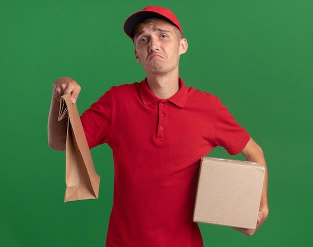 Déçu jeune livreur blonde détient un paquet de papier et une boîte en carton sur vert