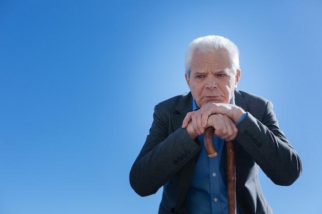 Déçu retraité malheureux malade rafraîchissant des souvenirs de sa vie et triste alors qu'il était assis dans le parc