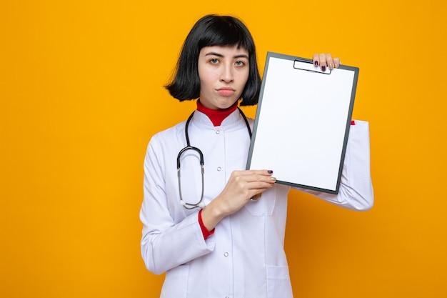 Déçue jeune jolie femme caucasienne en uniforme de médecin avec stéthoscope tenant le presse-papiers