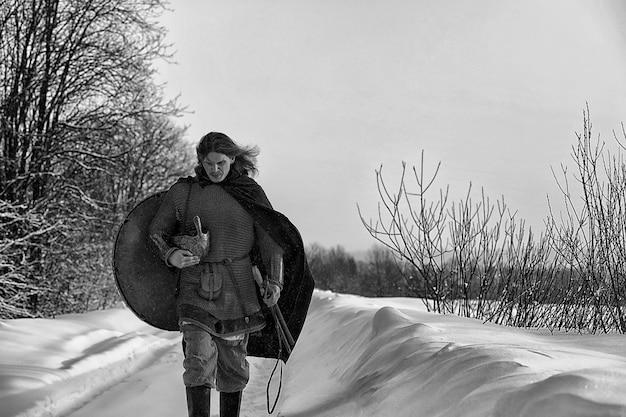 Défenseur du jeune guerrier en cotte de mailles armé d'une épée et d'une hache