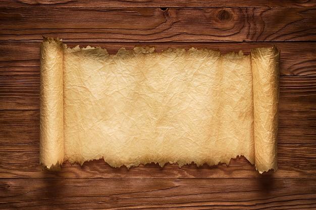 Défilement déplié sur une table en bois, vieux papier texture, mur