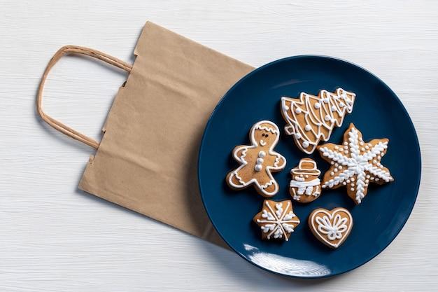 Définir les biscuits du nouvel an festif dans une assiette bleue sur fond de bois blanc