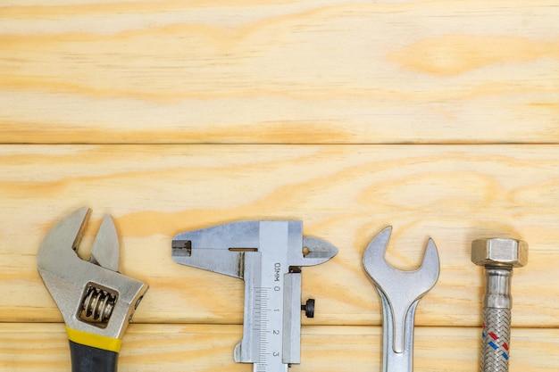 Définir les outils et le tuyau d'eau pour les plombiers sur des planches en bois avec un espace pour la publicité