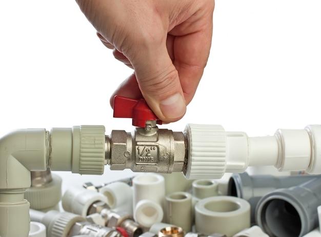 Définir les raccords de plomberie dans sa main isolé sur blanc