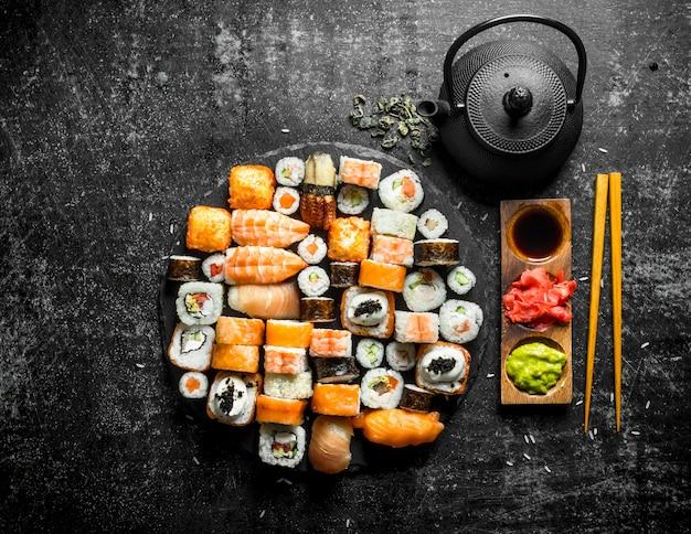 Définissez une variété de rouleaux, de sushis et de makis avec du thé vert. sur une surface rustique sombre