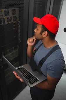 Défis informatiques. vue de dessus de l'ingénieur informatique rêveur touchant le menton et tenant un ordinateur portable