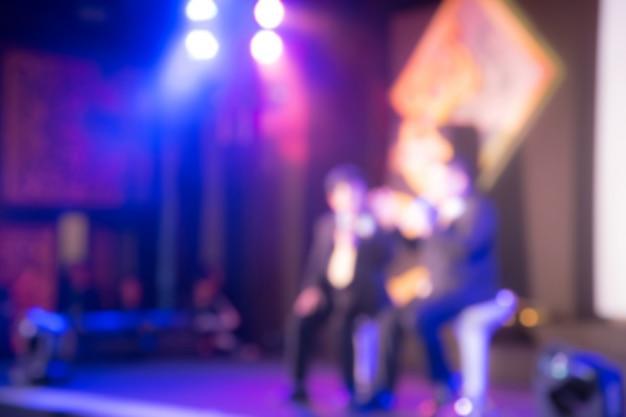 Défocalisation de deux intervenants sur la scène avec vue arrière du public dans la salle de conférence ou le séminaire, concept commercial et pédagogique