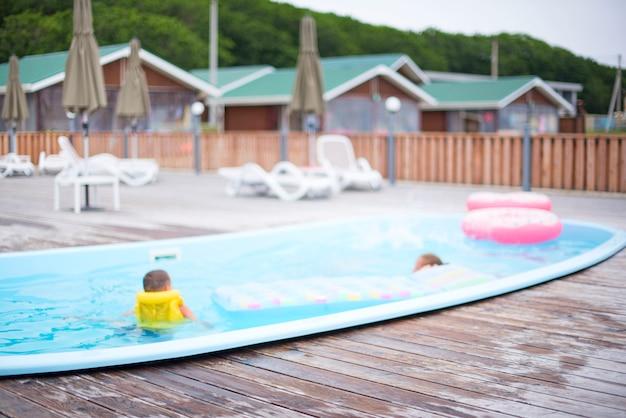 Défocalisation fond flou base loisirs maisons en bois piscine chaises longues sol en bois