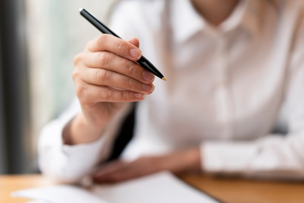 Défocalisé femme montrant stylo bouchent