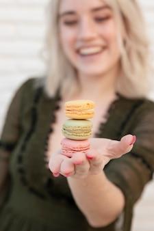 Défocalisé femme tenant des macarons et souriant