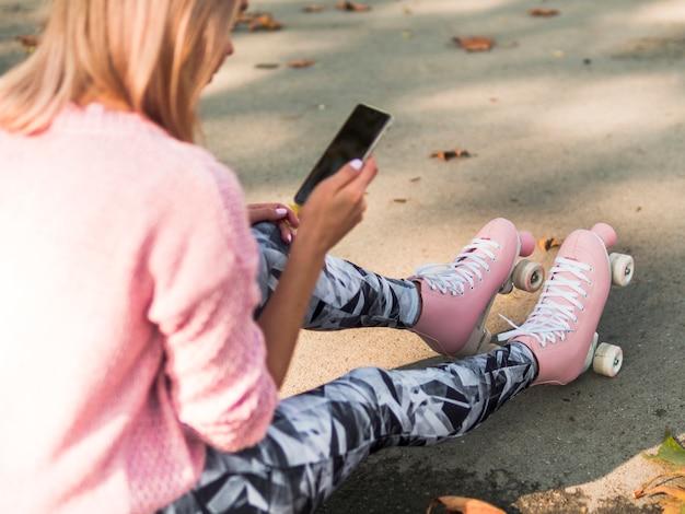 Défocalisé haute angle de femme en patins à roulettes à la recherche de smartphone