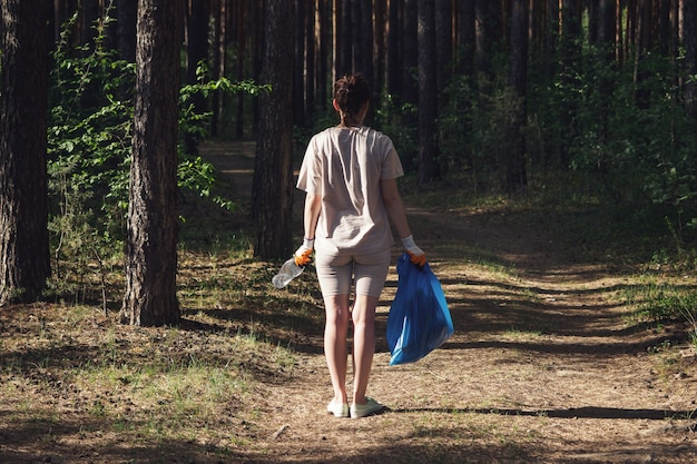 Dégager la forêt des déchets plastiques non recyclables. une jeune fille portant des gants ramasse les ordures dans un sac. sauver l'environnement d'une catastrophe écologique. volontaires, concept d'activistes éco.