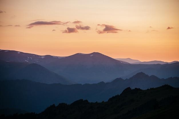 Dégradé chaud du ciel de l'aube au-dessus des couches de silhouettes de montagne et de roche.