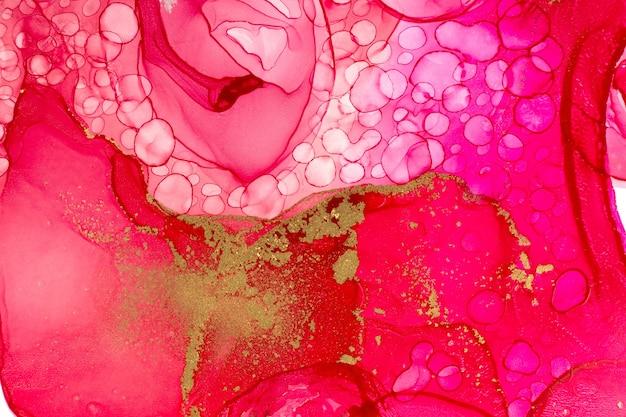Le dégradé d'encre aquarelle rose vif abstrait tombe avec des paillettes dorées.