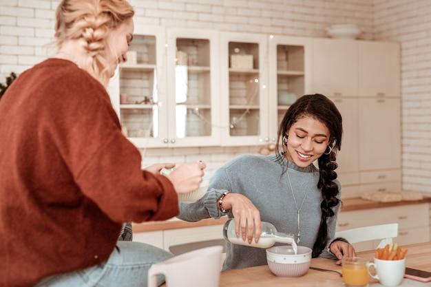 Dégustation d'un petit-déjeuner ordinaire. heureux fille afro-américaine avec une longue tresse luxuriante, verser le lait dans le bol du petit déjeuner
