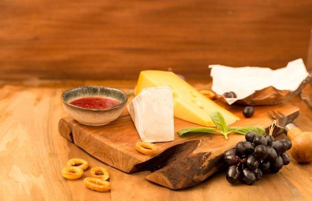 Dégustation d'un plat de fromages aux herbes et fruits sur une table en bois