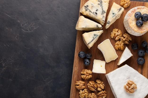 Dégustation d'un plateau de fromages sur une assiette en pierre sombre.