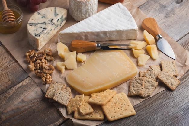 Dégustation d'un plateau de fromages sur un fond en bois.