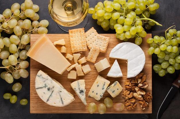 Dégustation d'un plateau de fromages sur une plaque de bois.