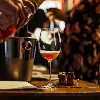 Dégustation de vin: sur une table en bois se trouve un verre de champagne rose.