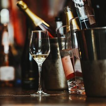 Dégustation de vin: un verre avec les restes de vin est sur la table à côté des seaux d'argent.