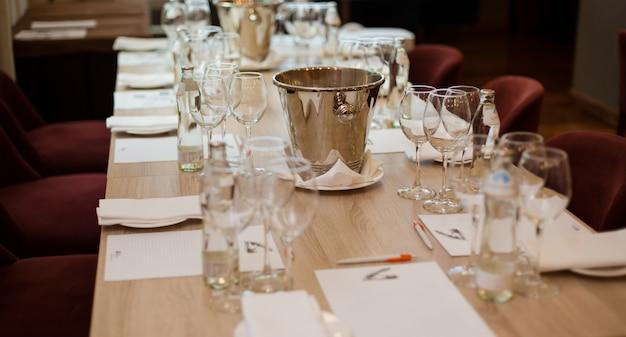 Dégustation de vins: table servie avec listes de dégustation, verres, bouteilles d'eau et crachoir.