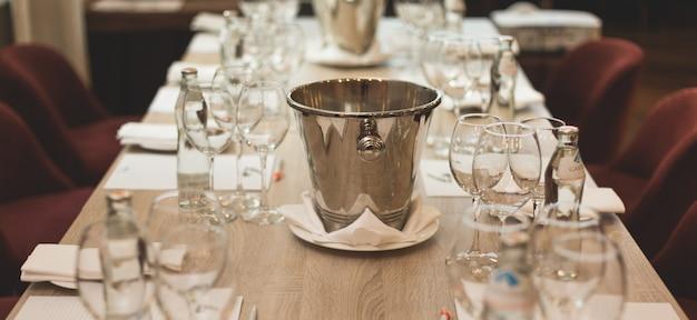 Dégustation de vins: table servie avec listes de dégustations, verres, bouteilles d'eau et crachoir.