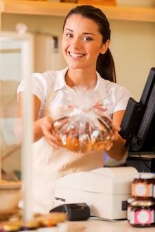 Dégustez des biscuits frais ! belle jeune caissière en tablier debout près de la caisse enregistreuse et étirant les cookies