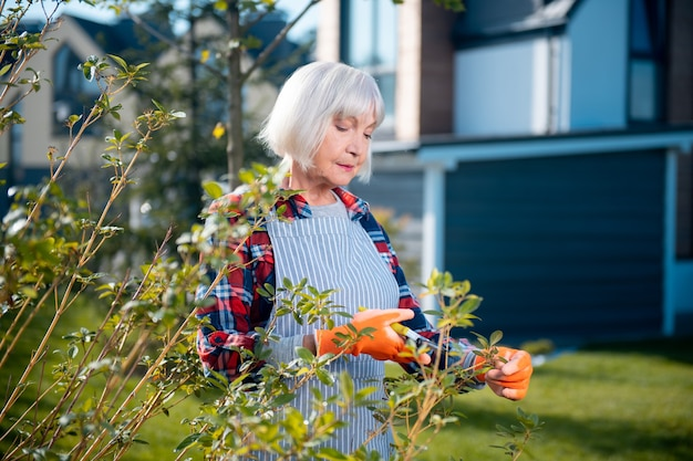 Dehors. gentille dame réfléchie, profitant du temps tout en se tenant dans le jardin