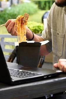 Déjeuner au parc en plein air. wok en boîte dans un récipient alimentaire noir, maquette. tenir des nouilles épicées avec des baguettes. service de livraison de restauration rapide. repas de rue chinois à emporter