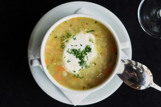 Déjeuner au restaurant. bol avec soupe servi avec un verre de vin rouge.