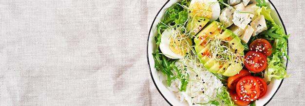 Déjeuner bol de bouddha végétarien vert sain avec des œufs, du riz, des tomates, des avocats et du fromage bleu sur la table.