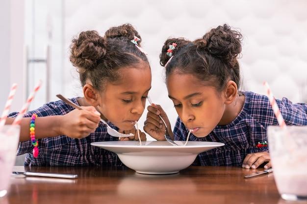 Déjeuner à la cafétéria. petits frères et sœurs mignons partageant des pâtes tout en mangeant leur déjeuner à la cafétéria après la maternelle