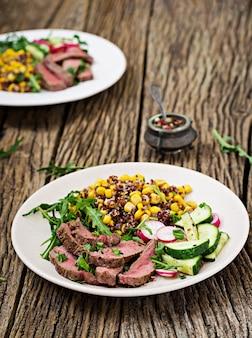 Déjeuner dans un bol avec steak de bœuf grillé et quinoa, maïs, concombre, radis et roquette