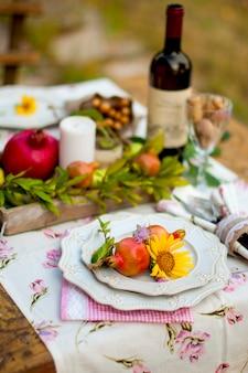 Déjeuner dans le jardin avec vin et fruits. dîner romantique en plein air. feuilles d'automne de fleurs. belle table de scrapbooking.