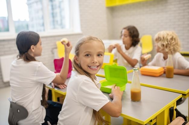 Le déjeuner. les écoliers en train de déjeuner dans la classe et l'air excité