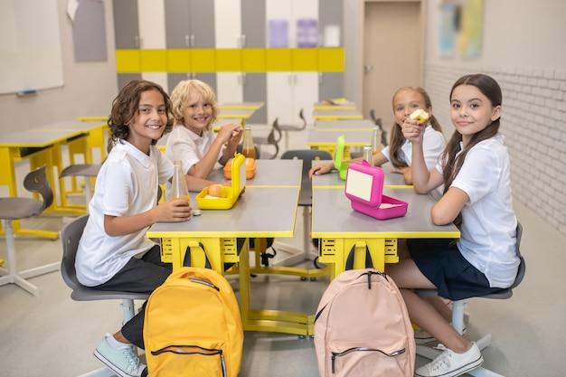 Le déjeuner. les écoliers en train de déjeuner dans la classe et l'air satisfait