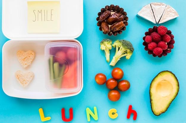 Déjeuner écrit près de la nourriture et de la boîte à lunch