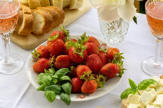 Déjeuner d'été à l'extérieur. table avec vin rosé et fraise